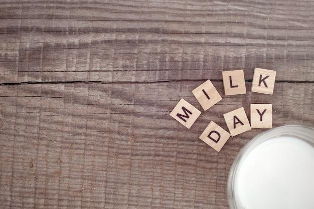 Drewniane litery dzień mleczny na starym drewnianym tle ze szklanką mleka w rogu. skopiuj miejsce.