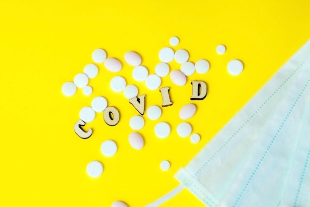 Drewniane litery są podszyte słowem covid, tabletki z maską medyczną. koncepcja na temat grypy, wirusa.