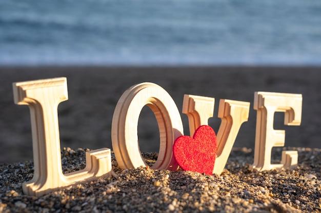 Drewniane litery tworzące słowo miłość z czerwonym sercem na brzegu morza. koncepcja kochanków