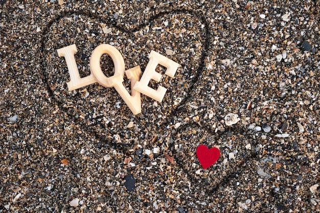 Drewniane litery tworzące słowo miłość z czerwonym sercem na piasku plażowym, wewnątrz serca wykonanego palcami. koncepcja san valentine