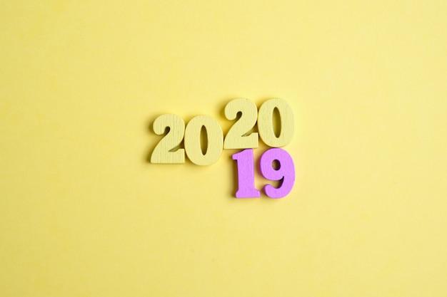 Drewniane litery w postaci liczb na żółtym tle. koncepcja roku zmienia się z 2019 na 2020.