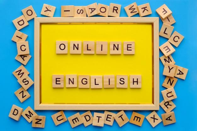 Drewniane litery z frazą angielski online w żółtej ramce na niebieskim tle.