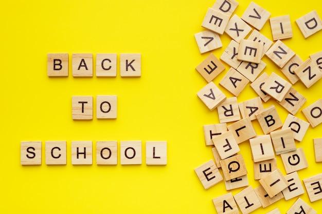 Drewniane litery z frazą z powrotem do szkoły na żółtym tle.