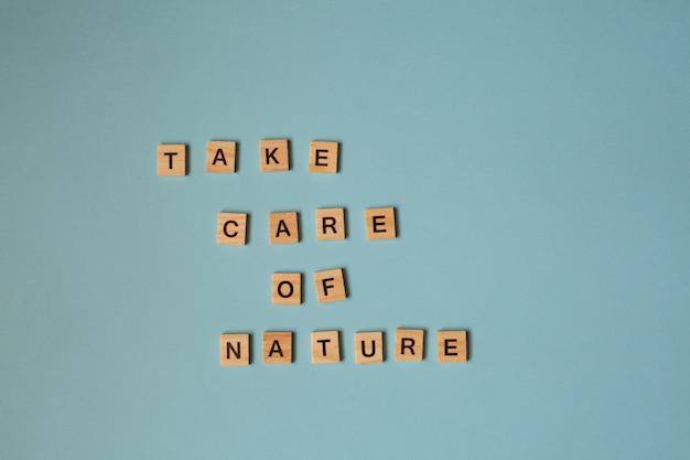 Drewniane litery z napisem dbają o naturę jasne drewniane litery na niebieskim tle