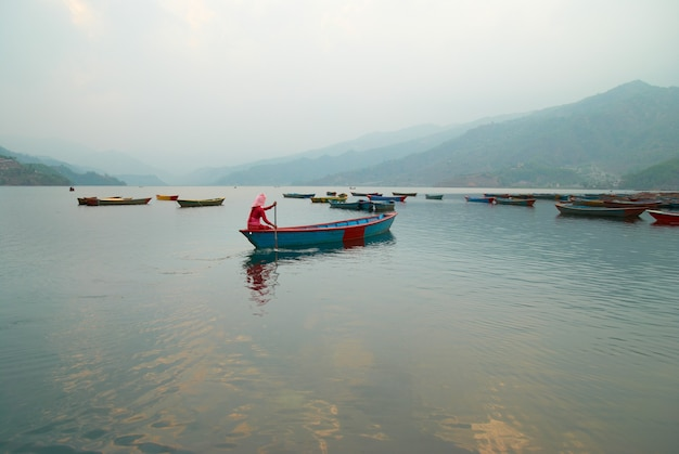 Drewniane łódki na jeziorze. nepalski wieczór.