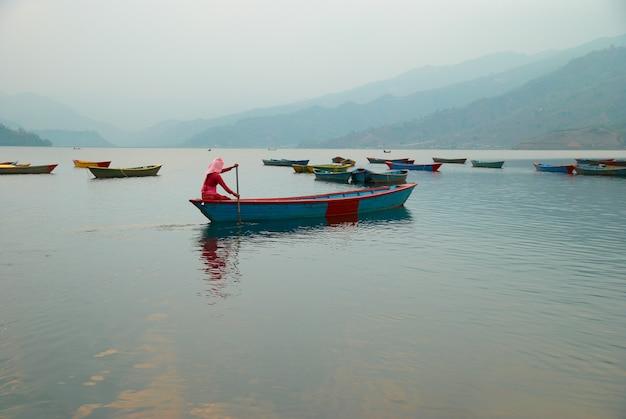 Drewniane łodzie na jeziorze. wieczór w nepalu.