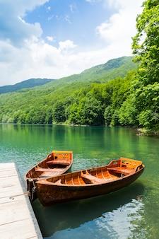 Drewniane łodzie na molo na górskim jeziorze