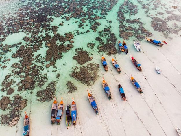 Drewniane łodzie z długim ogonem zakotwiczają na wybrzeżu z rafą koralową w morzu