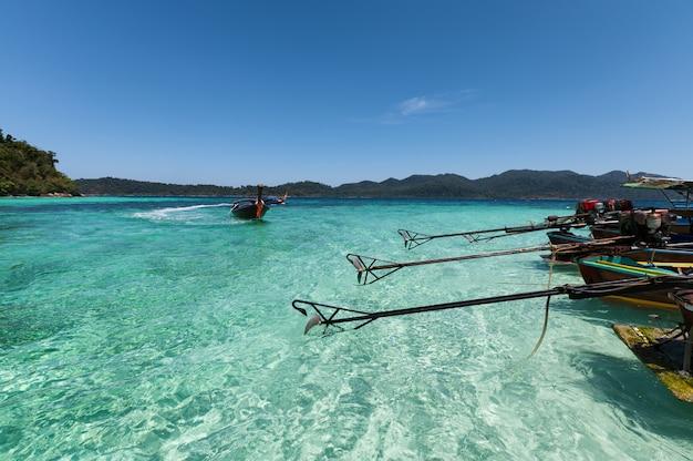 Drewniane łodzie z długim ogonem zakotwiczone na turkusowej wodzie