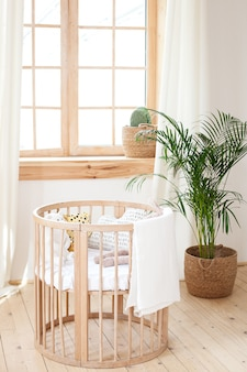 Drewniane łóżeczko w przedszkolu. ekologiczne łóżeczko z pościelą i pluszowymi zabawkami w uroczym pokoju dziecięcym z kwiatami w pomieszczeniach. pokój dziecięcy w stylu skandynawskim. rustykalne wnętrze. przytulny dom w stylu hygge.