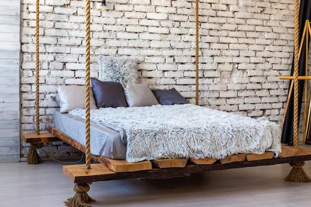 Drewniane łóżko z poduszkami i futrzanym kocem zawieszonym na linach w loftowym wnętrzu stylowej nowoczesnej sypialni. surowy skandynawski styl luksusowych mebli.