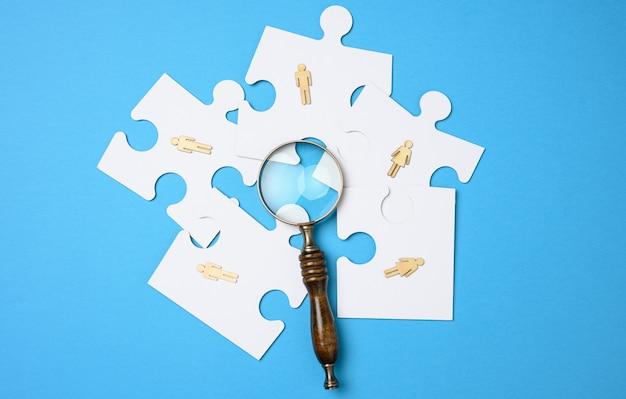 Drewniane ludziki leżą na białych puzzlach wokół lupy na niebieskim tle. koncepcja poszukiwania utalentowanych osób, rekrutacja personelu, identyfikacja zdolnych do awansu zawodowego
