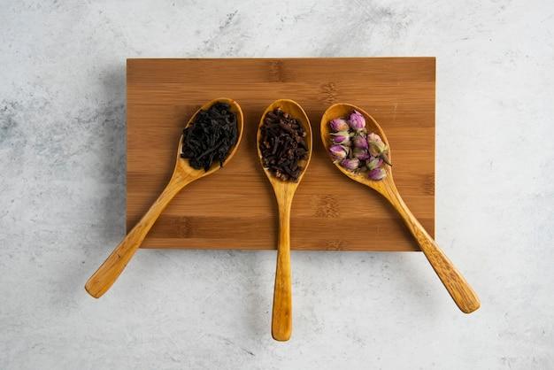 Drewniane łyżeczki z suszonymi różami, herbatkami sypkimi i goździkami.