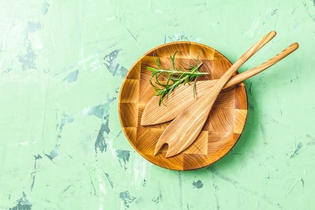 Drewniane łyżki do sałatki w drewnianym talerzu