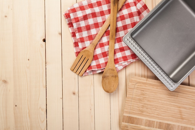 Drewniane łyżki i inne narzędzia kuchenne z czerwonymi serwetkami na kuchennym stole.