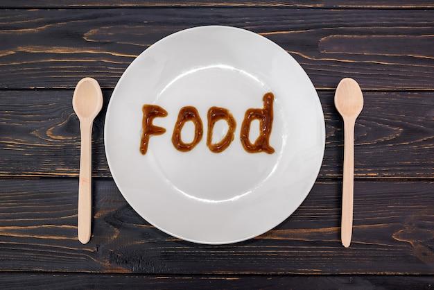 Drewniane łyżki i słowo jedzenie na białym talerzu. widok z góry.