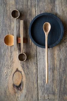 Drewniane łyżki i talerze z widokiem z góry, koncepcja ekologicznych sztućców, selektywne ustawianie ostrości