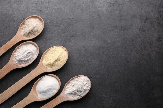 Drewniane łyżki z różnymi rodzajami mąki na szaro