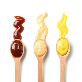 Drewniane łyżki z sosami odizolowywającymi na białym tle