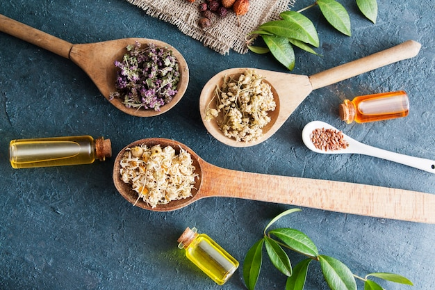 Drewniane łyżki z suszonymi ziołami leczniczymi i butelki z esencją. herbaty i nalewki lecznicze jako lek alternatywny