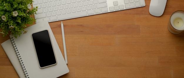 Drewniane miejsce do pracy z miejscem do kopiowania, urządzeniem komputerowym, smartfonem, notatnikami i dekoracjami