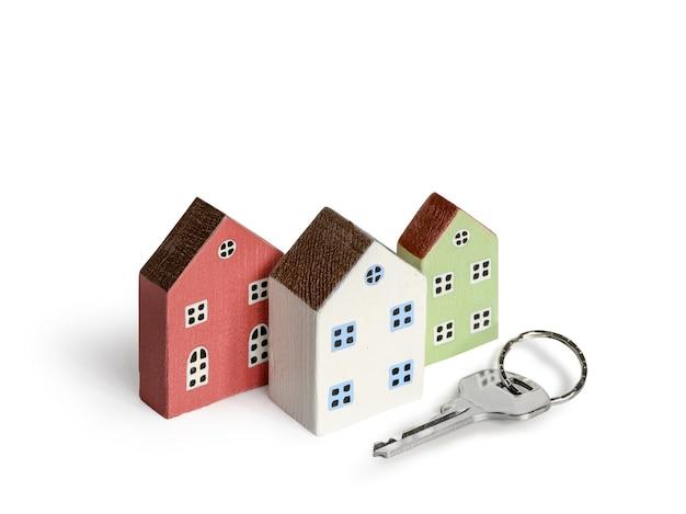 Drewniane miniaturowe domy i klucz dom na białym tle. nieruchomości, koncepcja ubezpieczenia, hipoteka, kupno sprzedam nowy dom.