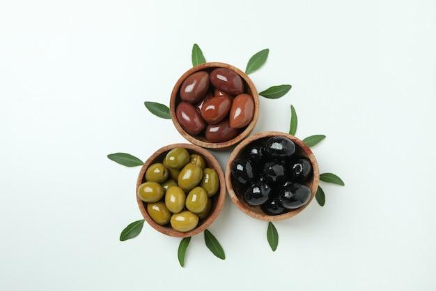 Drewniane miski oliwek i liści na białym tle