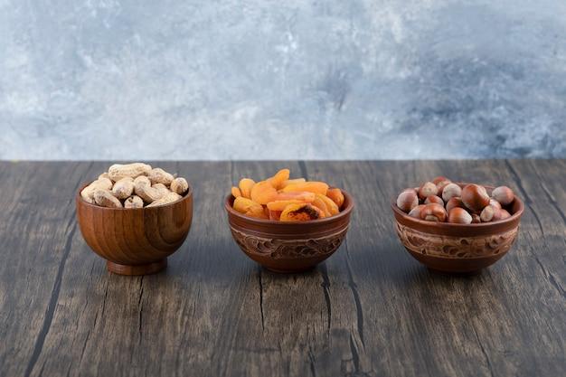 Drewniane miski pełne zdrowych orzechów z suszonymi owocami moreli na drewnianym stole.