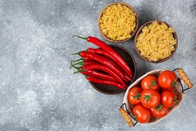 Drewniane miski surowego makaronu z czerwonymi papryczkami chili i pomidorami na marmurze.