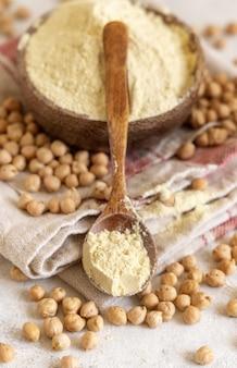 Drewniane miski surowej mąki z ciecierzycy i fasoli z łyżką, na białym stole z bliska