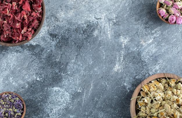 Drewniane miski suszonych kwiatów na marmurowym stole.