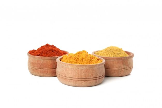 Drewniane miski z papryką, curry i kurkumą w proszku na białym tle