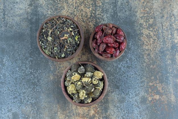 Drewniane miski z suszonymi kwiatami i owocami dzikiej róży.