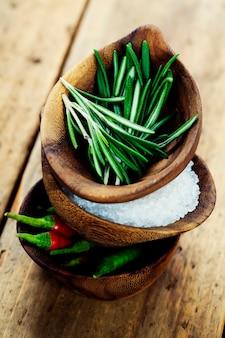 Drewniane miski ze świeżymi ziołami i przyprawami