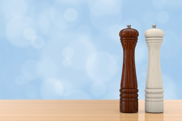 Drewniane młynki perrer lub młynek do soli przed niebieską ścianą na drewnianym stole. renderowanie 3d