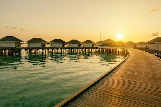 Drewniane molo i linia tropikalnych willi w czasie wschodu słońca, malediwy