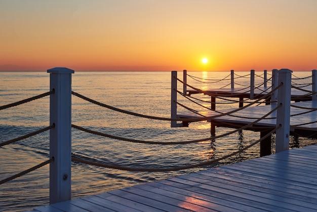 Drewniane molo na fantazyjnym pomarańczowym zachodzie słońca.