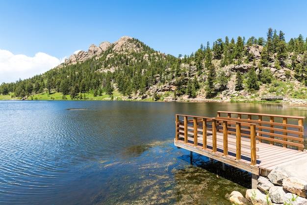 Drewniane molo na jeziorze na tle góry skalistej