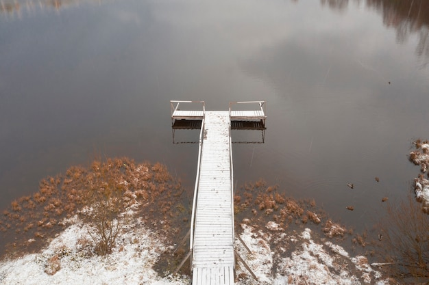 Drewniane molo nad jeziorem z kaczkami późną jesienią
