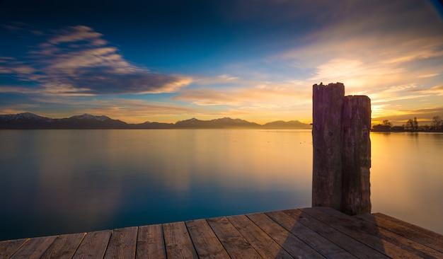 Drewniane molo nad spokojnym morzem z pasmem górskim i wschodem słońca
