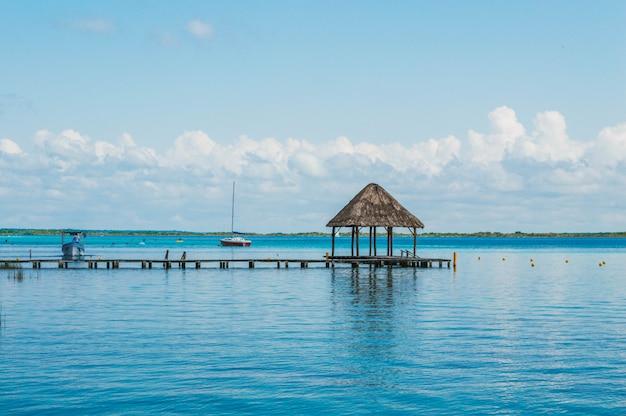 Drewniane molo w lagunie siedmiu kolorów z pięknym krajobrazem. krystalicznie czysta woda laguny bacalar, quintana roo, meksyk.
