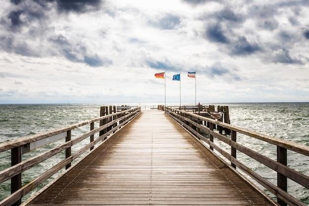 Drewniane molo z flagami. późne lato krajobraz z zachmurzonym niebem. tło wakacje. wybrzeże bałtyku, niemcy, cel podróży