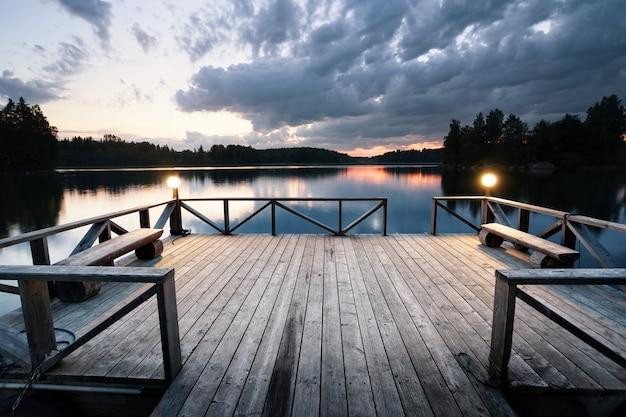 Drewniane molo z latarniami opuszczającymi jezioro