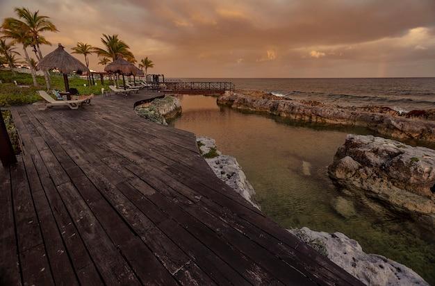 Drewniane molo z widokiem na morze o zmierzchu: widok zakładu balnerae w puerto aventuras w meksyku