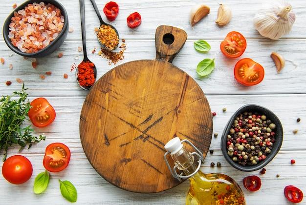 Drewniane naczynia do gotowania, pusta deska do krojenia i przyprawy