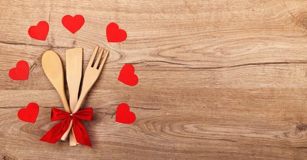Drewniane naczynia kuchenne z czerwoną kokardą, papierowe czerwone serca na drewnianym tle i miejsca na tekst.