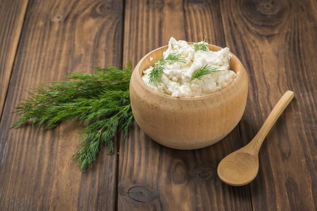 Drewniane naczynia ze świeżym domowym serem na drewnianym stole. pojęcie zdrowej diety.