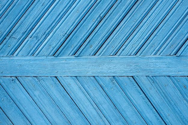 Drewniane niebieskie tło ze starą niebieską farbą i deskami po przekątnej