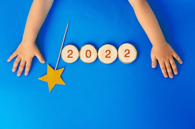 Drewniane numery 2022 na niebieskim tle papieru, widok z góry