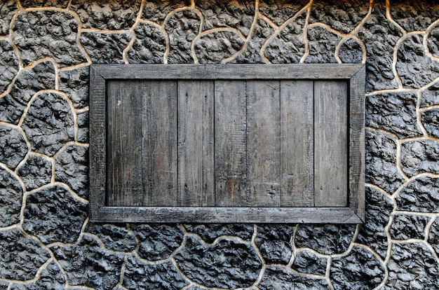 Drewniane okno w ścianie czarnego kamienia.